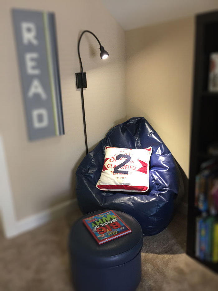 A cozy reading area for kids with bean bag, bookshelf and reading light.