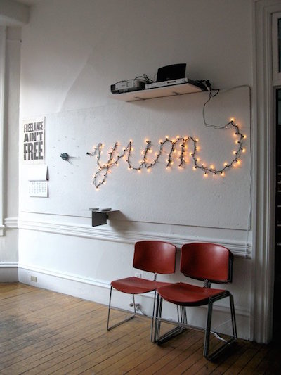 Words written with string light on walls as art