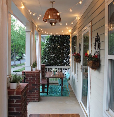 Colorful front porch with globe string lights